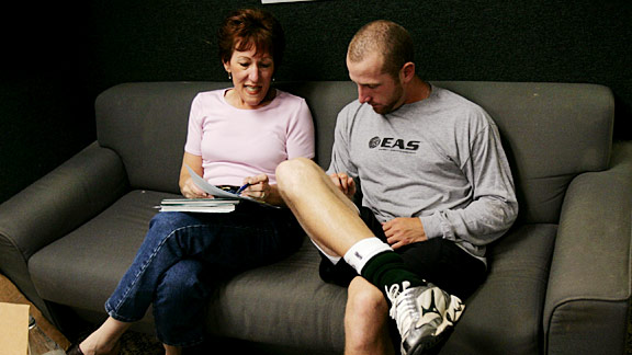 Pam Pitts reviews a contract with A's pitcher Dallas Braden.