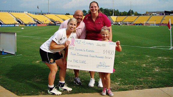 McCall Zerboni, left, and Emma Bayer, right, pose with Bayer's parents, Dave and Carey, and a check representing the proceeds from last year's auction.