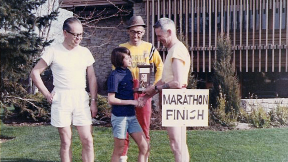 Maureen Wilton Mancuso poses for a photo to receive her marathon trophy. Coach Sy Mah stands behind the 13-year-old.