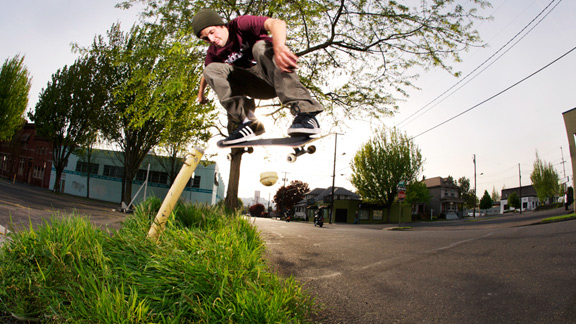 Jordan Sanchez backside 180s over lush greenery in the great Northwest.