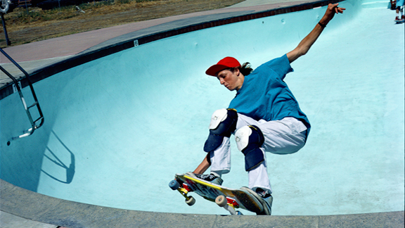 Tony Hawk frontside grinds a pool in 1986 and helps communities around the country build them in 2012.