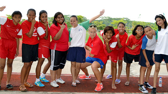 Valerie Henderson and Special Olympics Singapore players strike a pose that is part of their goal celebration.