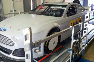 The new Gen 6 Sprint Cup car goes through inspection on NASCAR's new state-of-the-art laser platform designed to measure approximately 40 points.