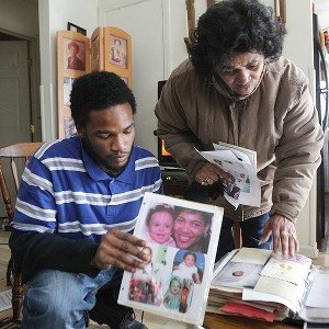 Master Lollar, brother of Richard Lollar, and Faye Lollar, an aunt, flip through a family photo album. Richard Lollar and Jacinth Baker were knifed to death outside an Atlanta nightclub 13 years ago.
