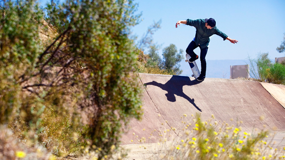 Geoff Rowley backside noseblunts in a desert ditch.