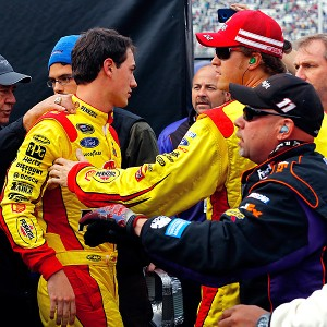 Joey Logano is restrained by a crew member after an altercation with Denny Hamlin following the Sprint Cup race at Bristol.