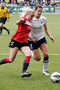 More than 16,000 fans watched Portland's Kathryn Williamson, left, battle with Seattle's Emily Zurrer during the first half Sunday.
