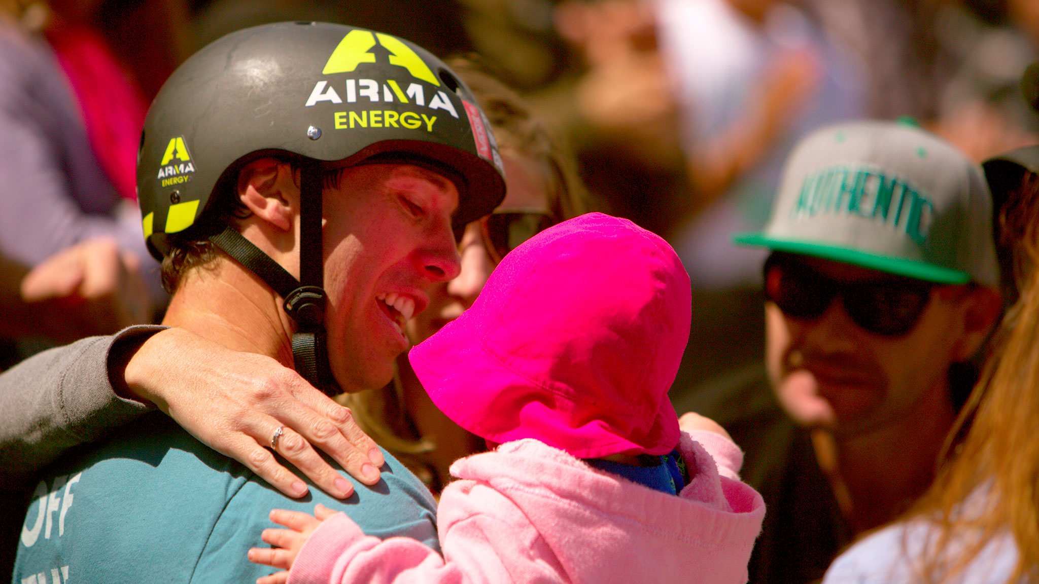 BMX Park gold medalist Gary Young holds his infant daughter, Leena, in front of the cheering fans.