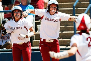 Oklahoma's Destinee Martinez, left, and Callie Parsons cheer for Brianna Turang (2) as she runs to home plate during a six-run third inning.