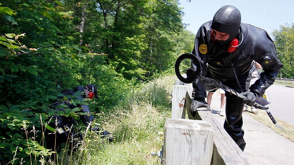 On June 24, Massachusetts state troopers search the woods along a street near Hernandez's home.