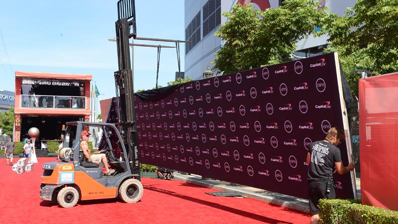 Placing the step and repeat background on the Red Carpet behind the scenes before The 2013 ESPYS.