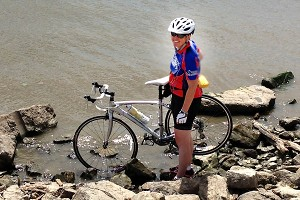 Heather Burns makes her RAGBRAI journey official by dipping her tires in the Mississippi River.