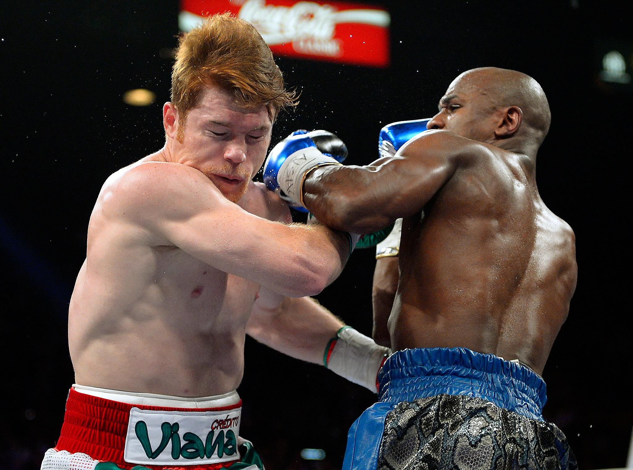 Floyd Mayweather Jr. punches Canelo Alvarez