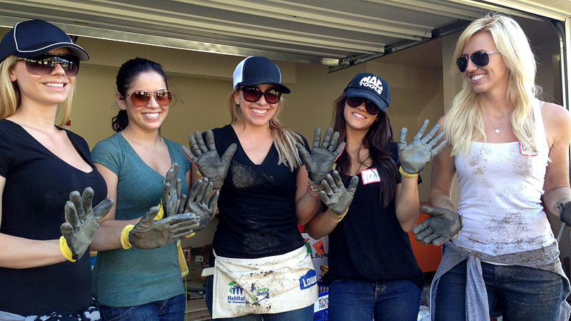 Brittany Force, middle, her sister Courtney, far right, and their friends and teammates helped transform a barren lot into a backyard for two families in Santa Ana, Calif.