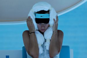Maria Sharapova wraps an ice-filled towel around her head during a changeover in her second-round match against Karin Knapp. The stifling heat forced the suspension of several matches on Day 4 of the Australian Open.