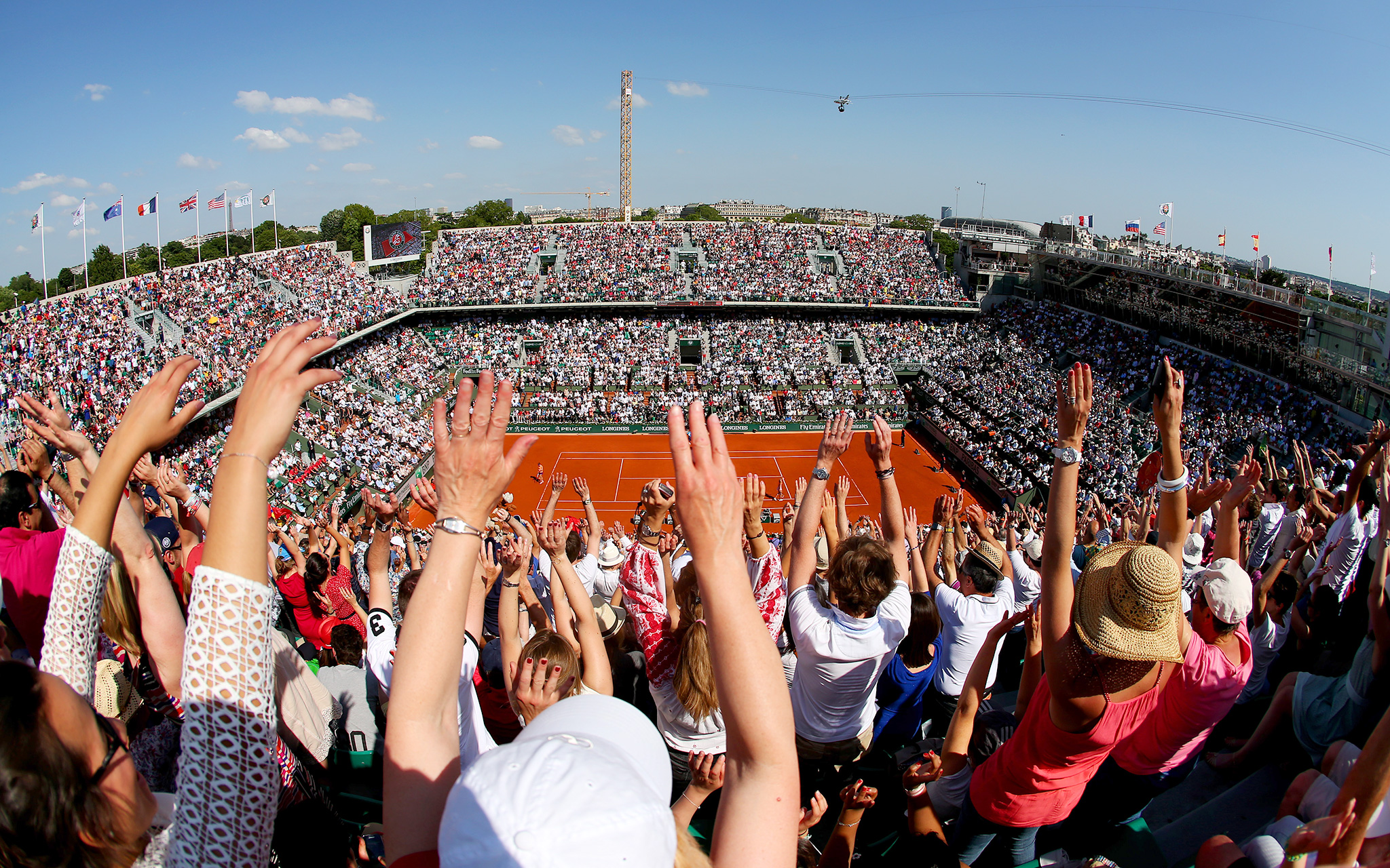 Fans at Court Philippe Chatrier do the wave during the women's singles final between Simona Halep and eventual champion Maria Sharapova.