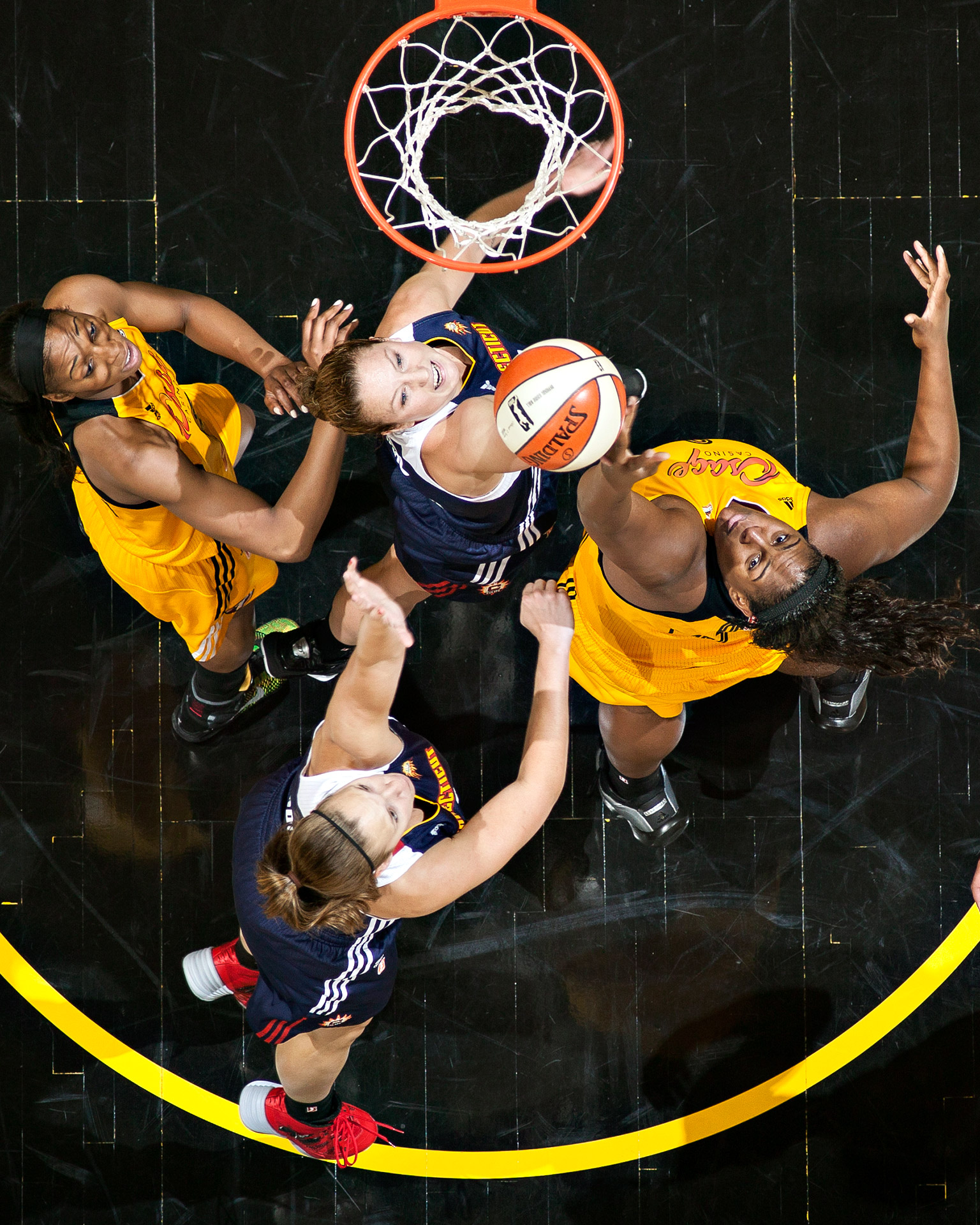 The Connecticut Sun's Kelsey Griffin (5) and Kayla Pedersen (7) rebound against the Tulsa Shock's Glory Johnson (25) and Courtney Paris (3) during their WNBA game at the BOK Center in Tulsa, Oklahoma.