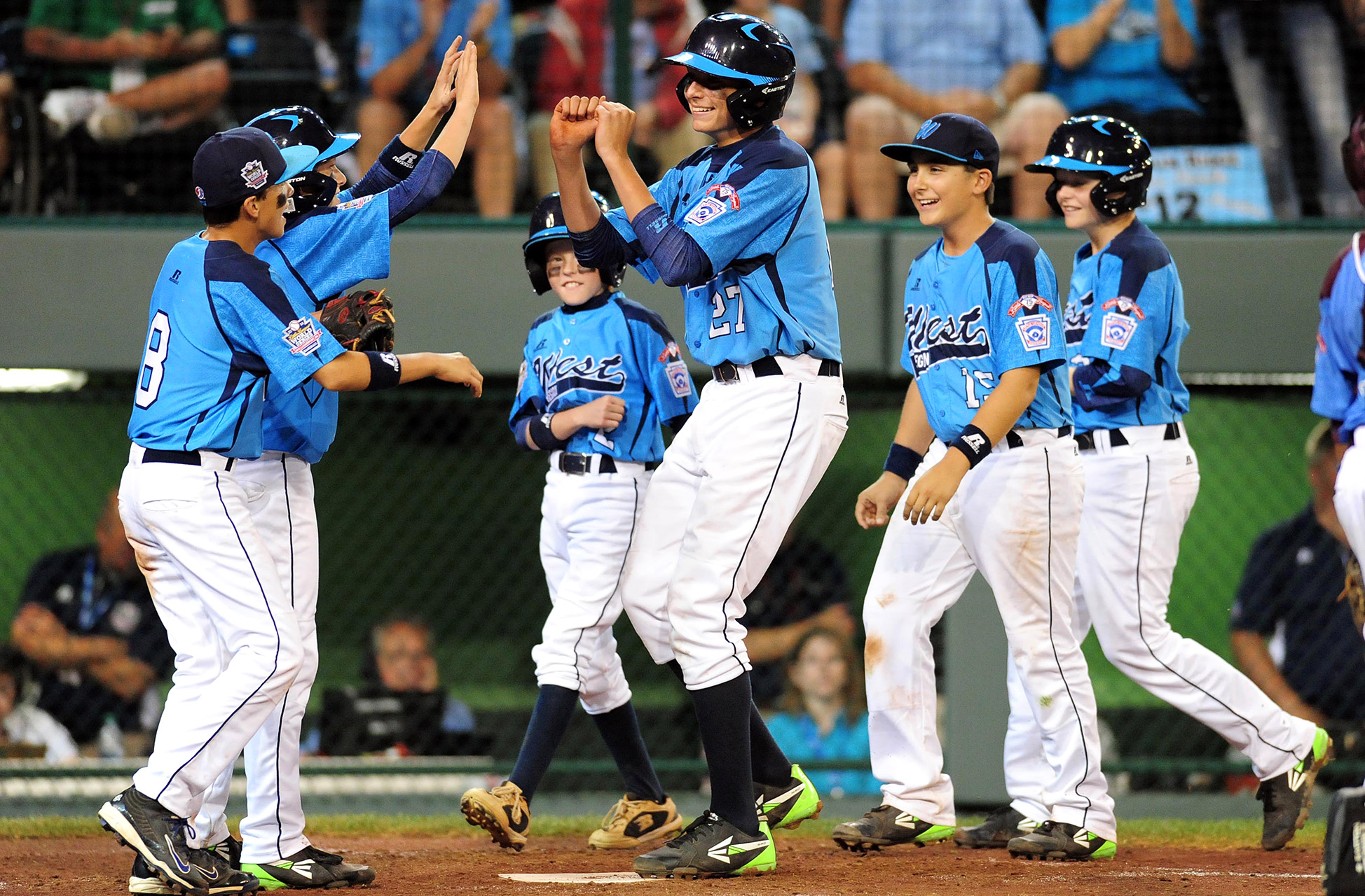 Las Vegas first baseman Brennan Holligan is met at home plate by his teammates after homering in his team's 8-1 win over Philadelphia at the Little League World Series.