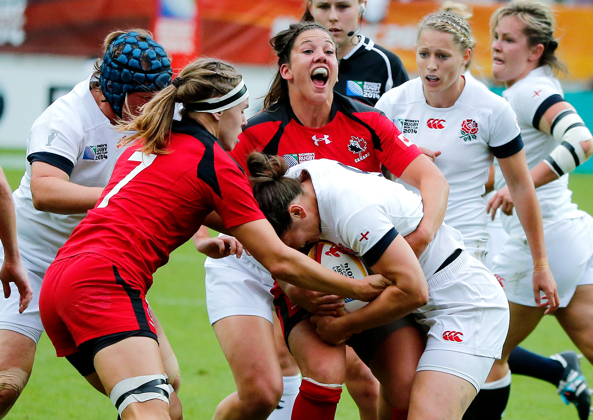England's Katy McLean, center, is tackled by Jessica Dovanne, right, and Karen Paquin, left, during the final match of the women's rugby World Cup against Canada at Jean Bouin Stadium in Paris. England defeated Canada 21-9.