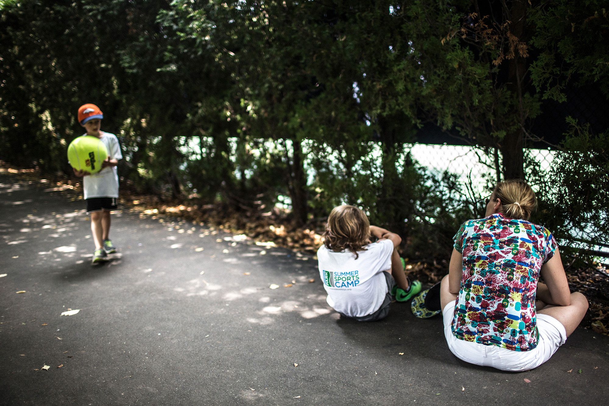 A mother and her two young sons escaped the heat and the crowds and took a break behind the court in a rare shady area.