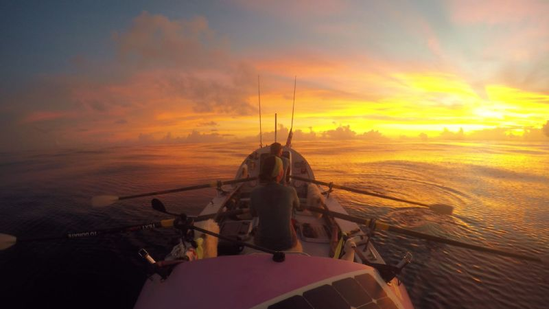 Two members of the Coxless Crew take in the sunset on the Pacific Ocean. Their pink Rossiter row boat is 29-feet-long and 7-feet-wide. It's made mainly of carbon fiber and named Doris.