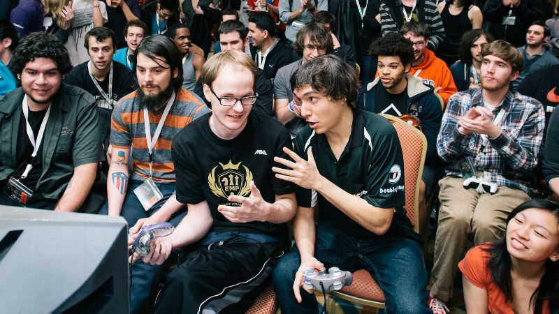 Pictured in black and gold, second from the left: Mew2King competes in the Doubles Grand Finals at Apex 2014 against Joseph Mango Marquez and Joey Lucky Aldama.