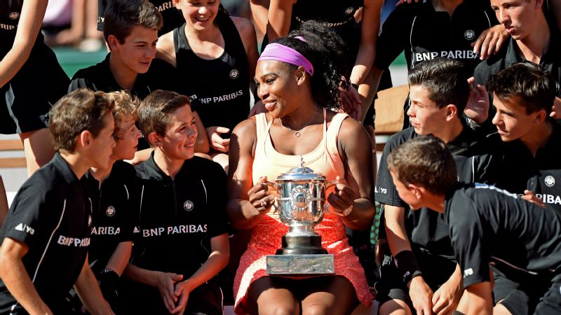 Serena Williams holds her French Open trophy and gathers with the tournament's ball boys and ball girls.