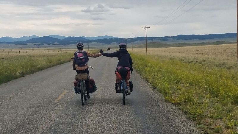 Taylor (left) and Meghan (right) high-five on a brief moment of flat, paved road in Colorado after descending Boreas Pass. I remember we were cold and exhausted and damp from rain, Whelan says, but feeling giddy and really proud of each other.