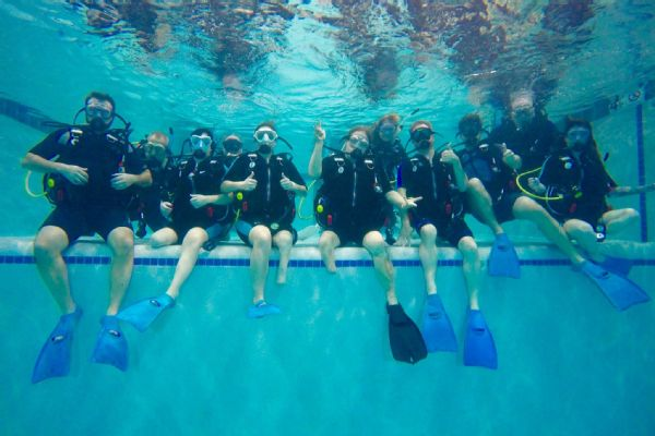 Emily Harvey (fifth from the left, with two thumbs up) testing out a Scuba class. Her nonprofit, LIM359, helps connect people with limb loss or limb difference to new activities and experiences.