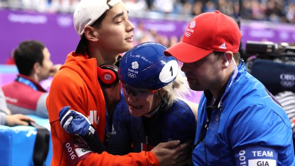 British medal hope Elise Christie is comforted by her partner, the Hungarian speedskater Shaolin Liu, and a Team GB official.