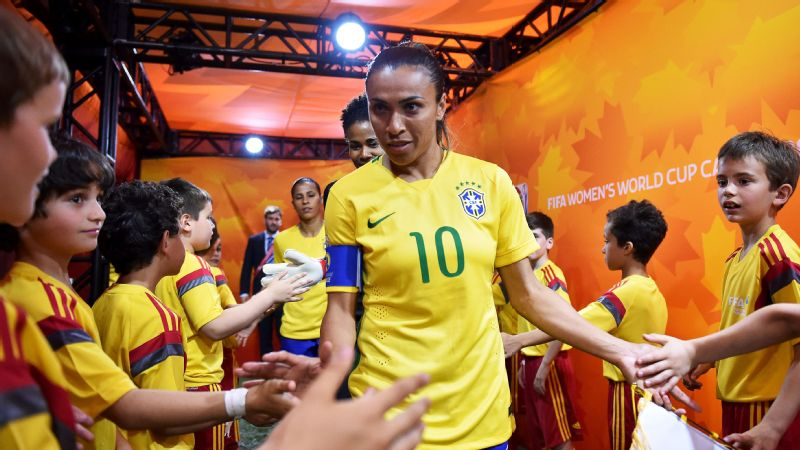 Marta greets children in the players' tunnel during the 2015 World Cup.