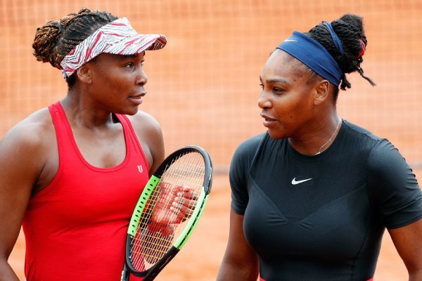 Serena Williams of the U.S., right, and her sister Venus Williams talk during their doubles second round match of the French Open tennis tournament against Italy's Sara Errani and Belgium's Kirsten Flipkens at the Roland Garros stadium, Friday, June 1, 20