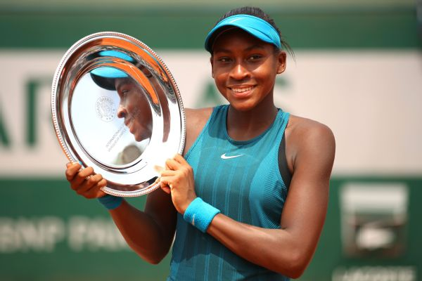 Cori Gauff of The United States celebrates victory with the trophy following the girls singles final against Caty McNally