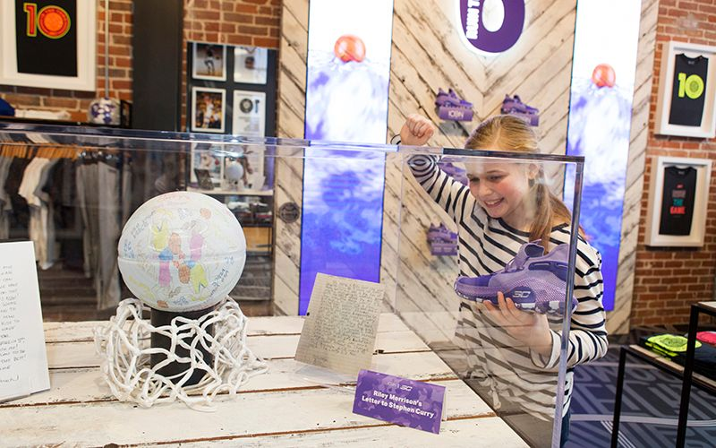 Riley peeking into the display case of the letter she originally wrote to Steph Curry at the Under Armour Store in Oakland.