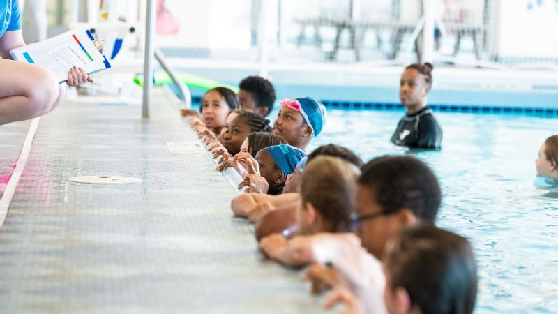 Students of LeBron James' I Promise school line up for swim instruction. The young swimmers began each day with a video message from Olympian Simone Manuel, who visited their school in March to announce the program.