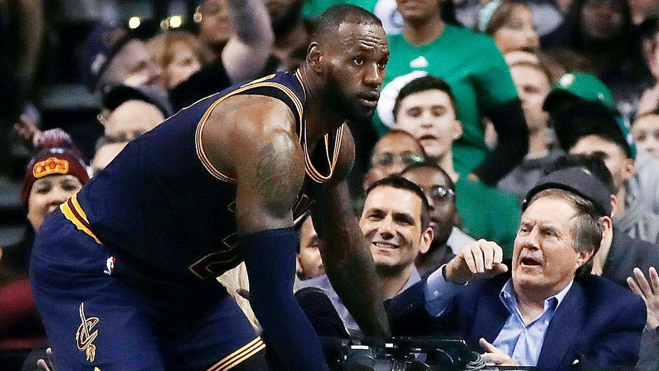 2d1f2605 Cleveland Cavaliers' LeBron James nearly tumbles onto New England Patriots  coach Bill Belichick sitting courtside